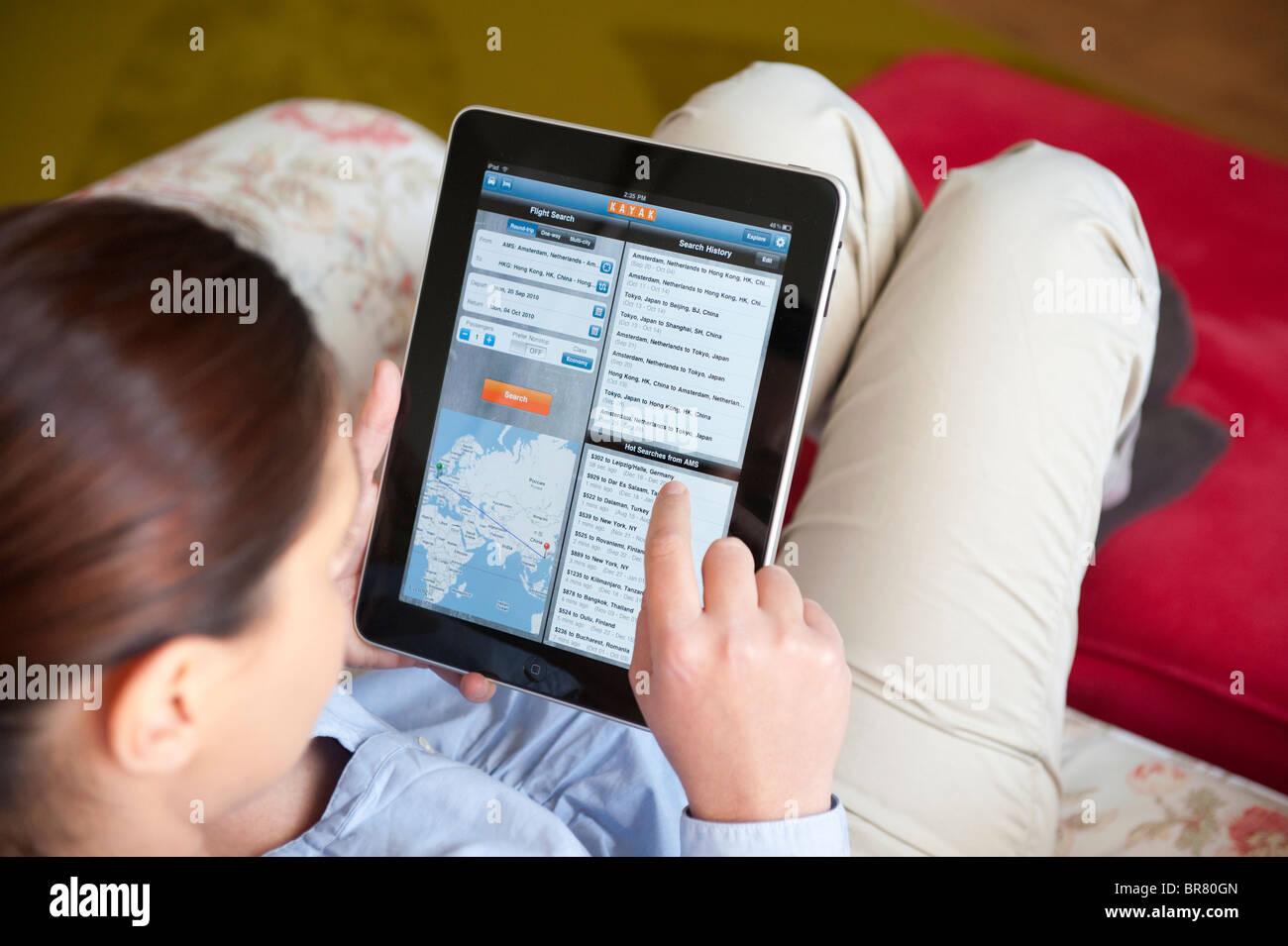 Donna che utilizza computer tablet iPad per prenotare vacanza on-line utilizzando Kayak applicazione di viaggio Immagini Stock