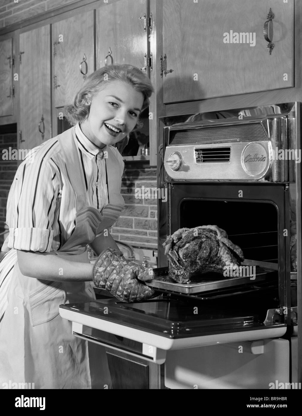 Anni Cinquanta donna sorridente casalinga indossando il grembiule tenendo  grandi arrosti di carni bovine provenienti da FORNO ELETTRICO IN CUCINA  guardando ... 8229ecffa857