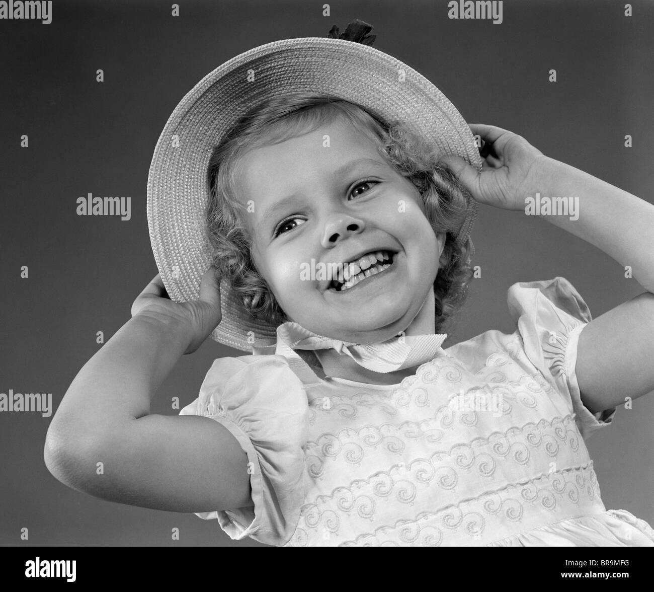 Anni Cinquanta bambino sorridente bambina indossa piuttosto il vestito e  cappello di paglia Immagini Stock 8020d5b4ff3d