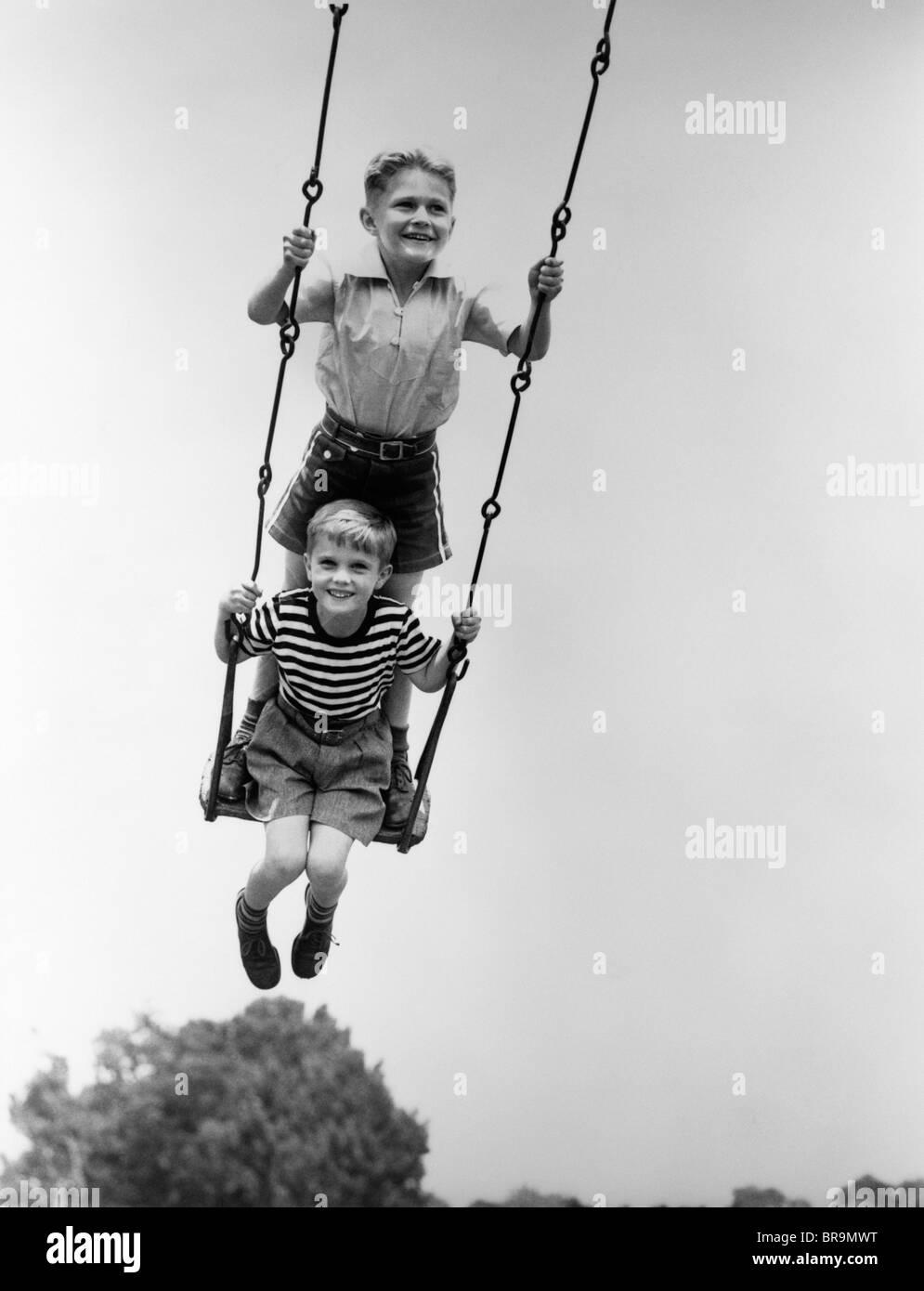 Negli anni Trenta due ragazzi sorridenti seduto in piedi SUL PARCO GIOCHI SWING Immagini Stock