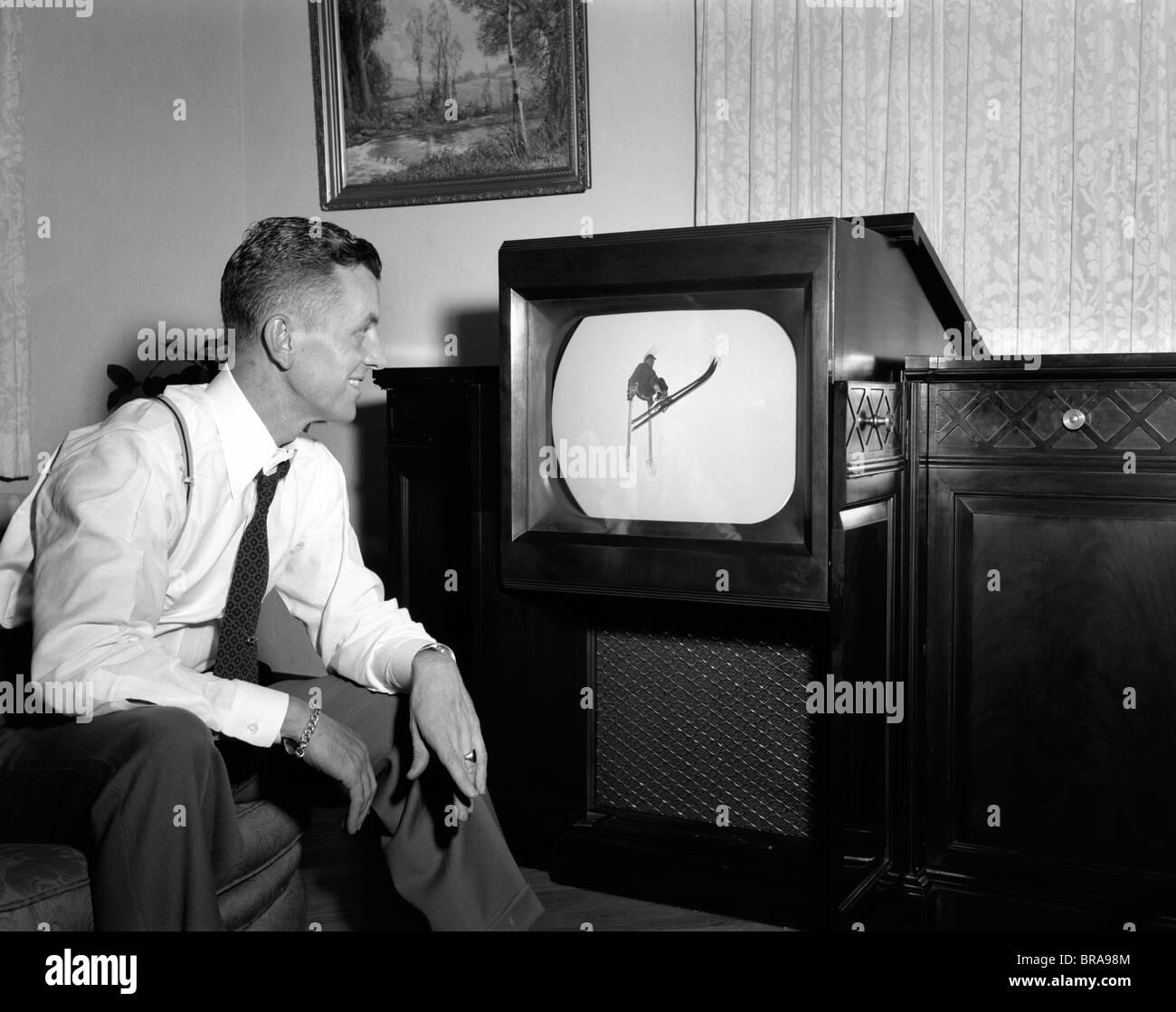 Negli anni quaranta anni cinquanta uomo sorridente a casa a guardare i programmi sportivi in televisione Immagini Stock