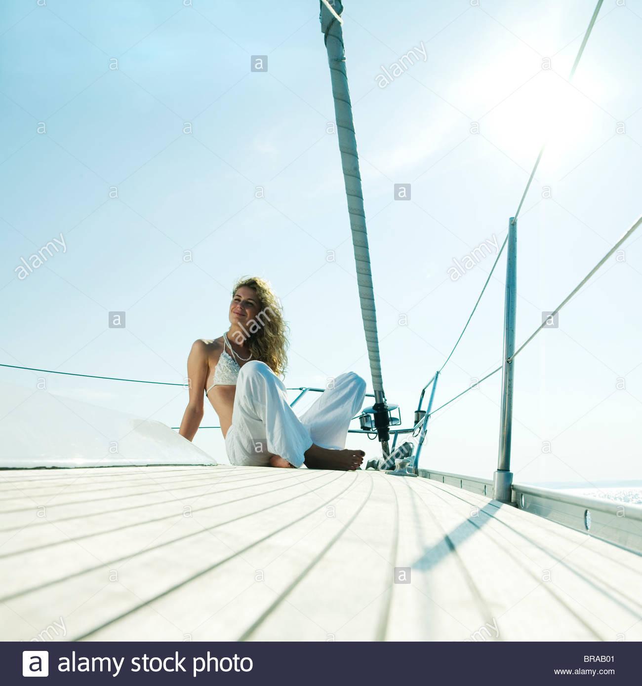 Donna seduta sulla prua di un 46ft yacht a vela, crociera spento la costa dalmata nel mare Adriatico, Croazia. Immagini Stock