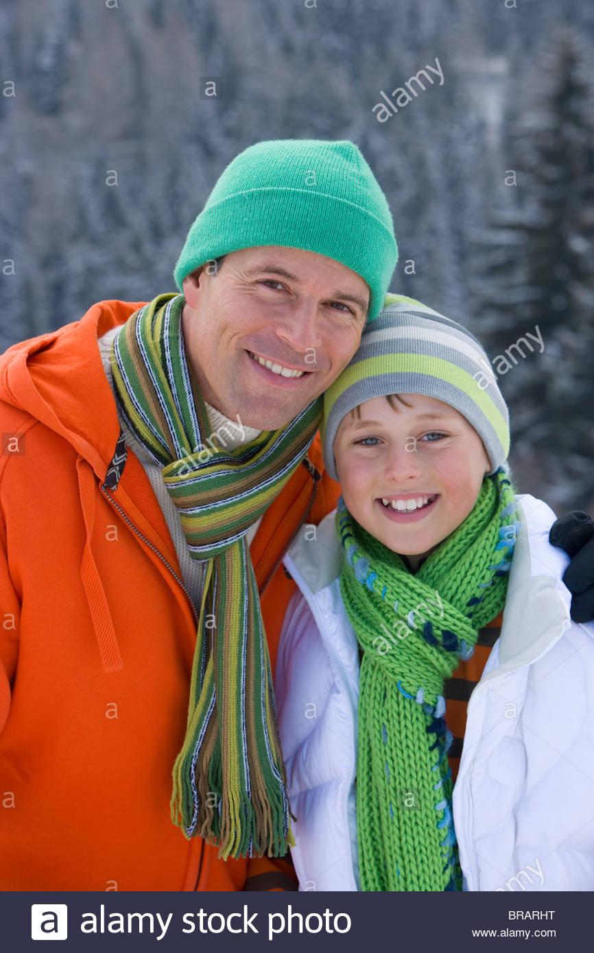 Padre e figlio nel cappuccio e sciarpa sorridente insieme all'aperto Immagini Stock