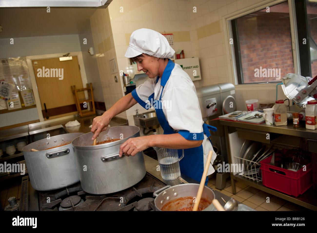 Scuola cuoco prepara la cena in una scuola primaria cucina, REGNO UNITO Foto Stock