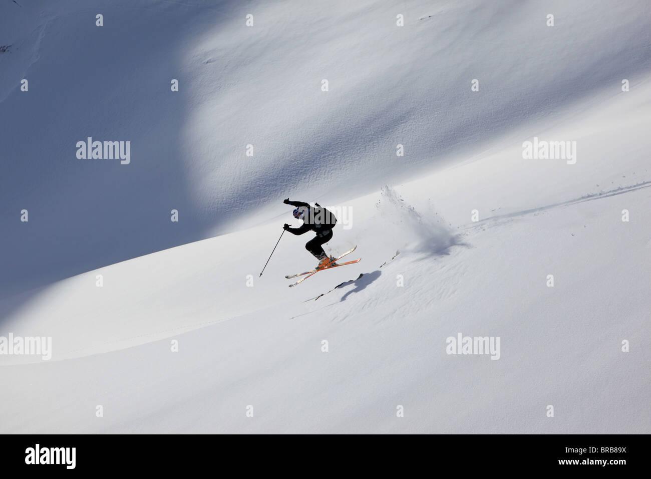 Uno sciatore salta alcune rocce in polvere su un Val Gardena i fuori pista Slope Immagini Stock