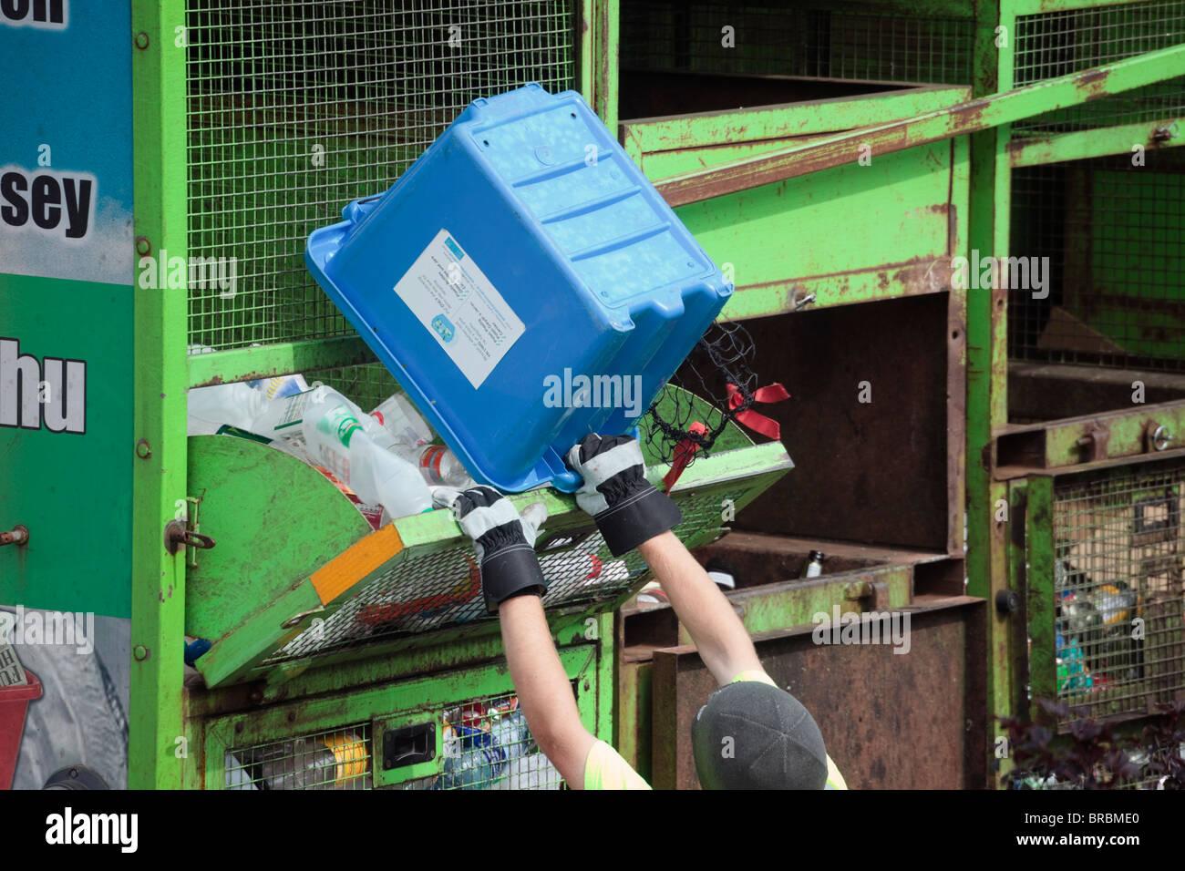 Workman raccolta riciclaggio casella di svuotamento di bottiglie di plastica nel carrello come parte della gestione Immagini Stock