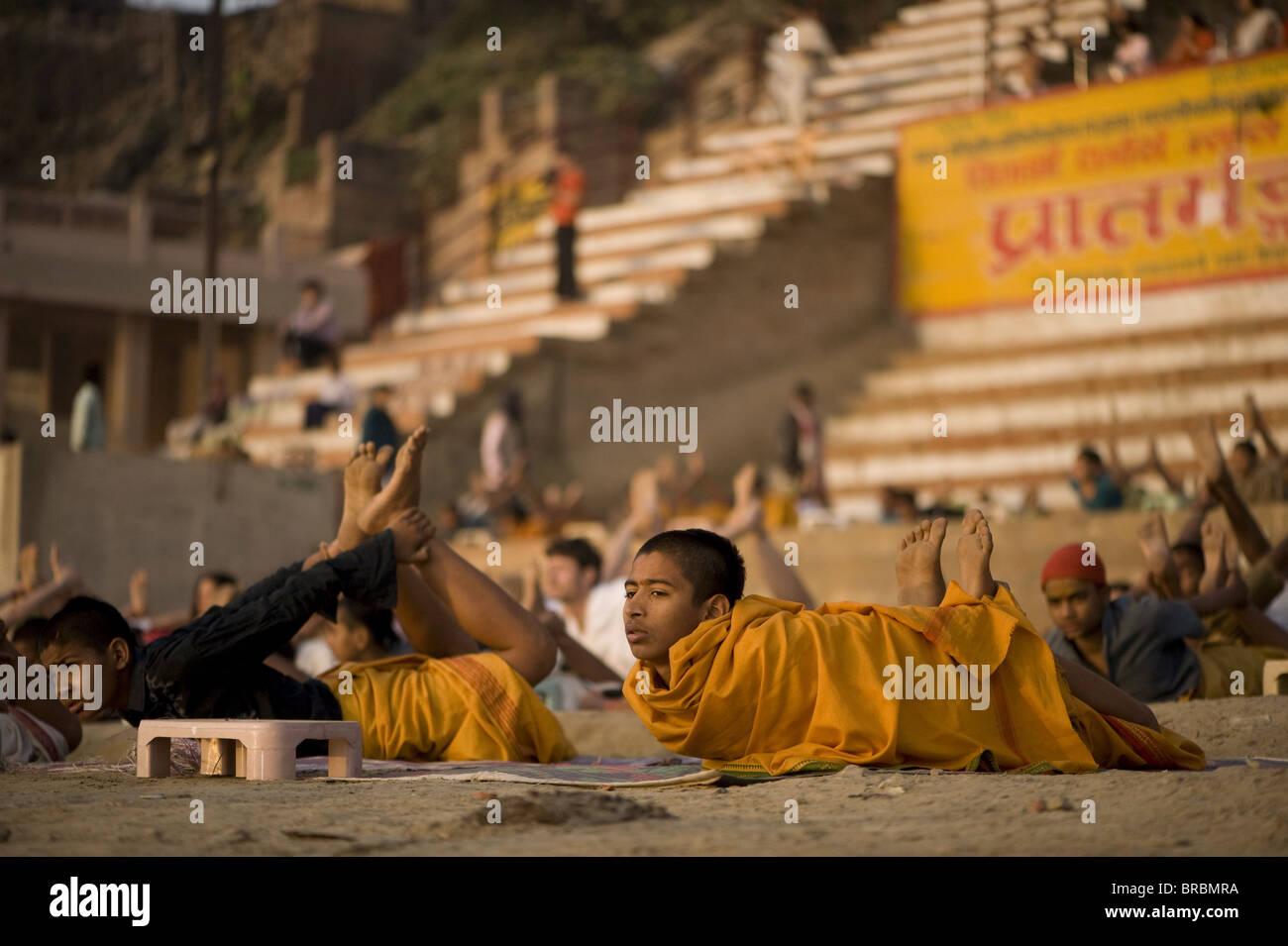 Gli studenti della scuola di Sanscrito tenendo la loro quotidiana lezione di yoga all'alba, su un ghat di Varanasi, Immagini Stock