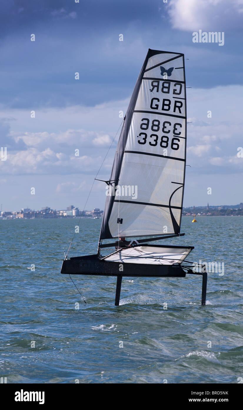 Trasferimento a caldo la vela Dinghy aliscafo Moth velocità rapida in 10kts di vento Immagini Stock