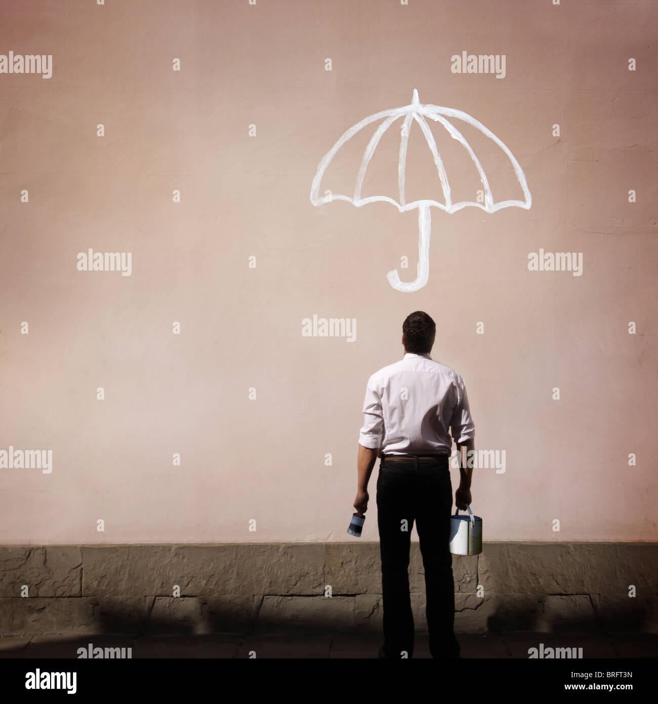 Uomo con vaso di vernice guardando una parete con ombrello dipinto su di esso Immagini Stock