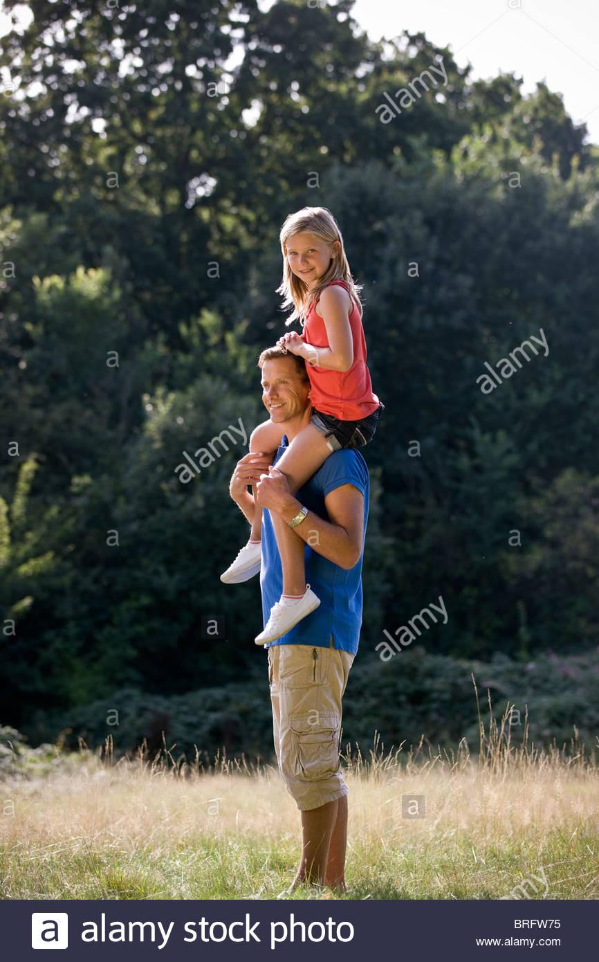 Un padre portando la sua figlia sulle sue spalle Immagini Stock