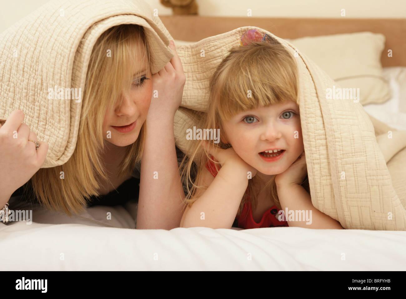 Due sorelle che giocano insieme sotto le lenzuola. Immagini Stock