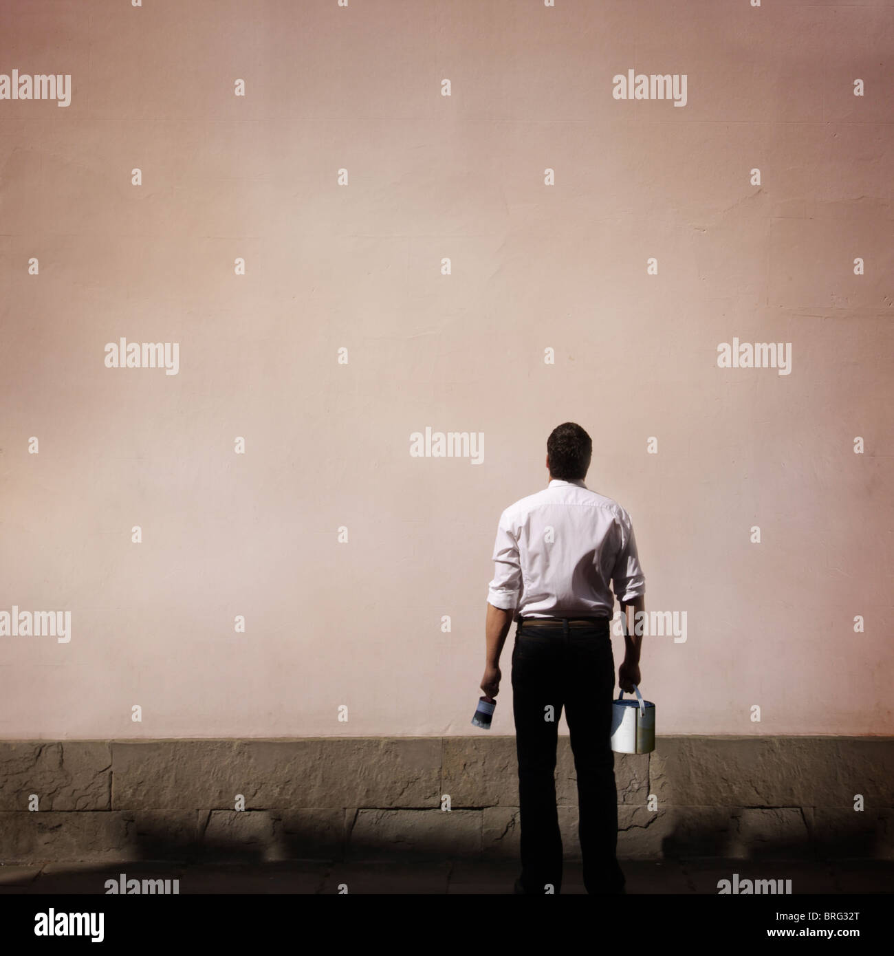 Uomo con vernice guardando un muro grezzo Immagini Stock