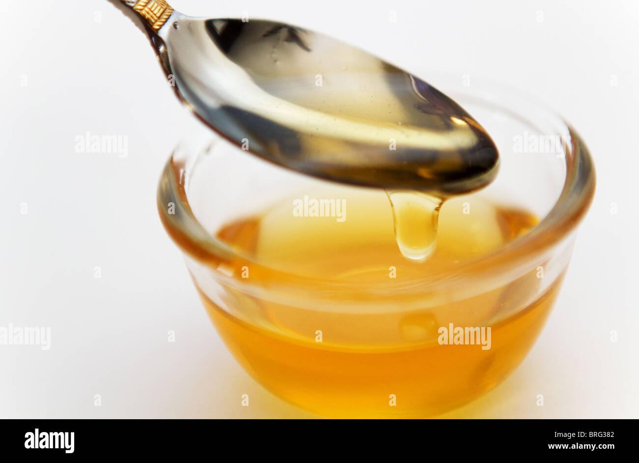 Il miele dorato gocciolare da un cucchiaio Immagini Stock