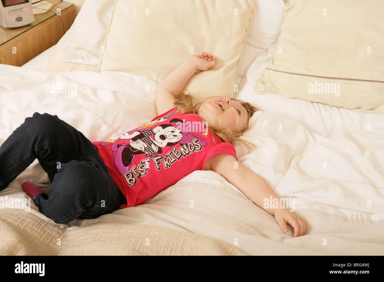 Una bambina di tre anni sdraiata sulla schiena in un letto grande. Immagini Stock
