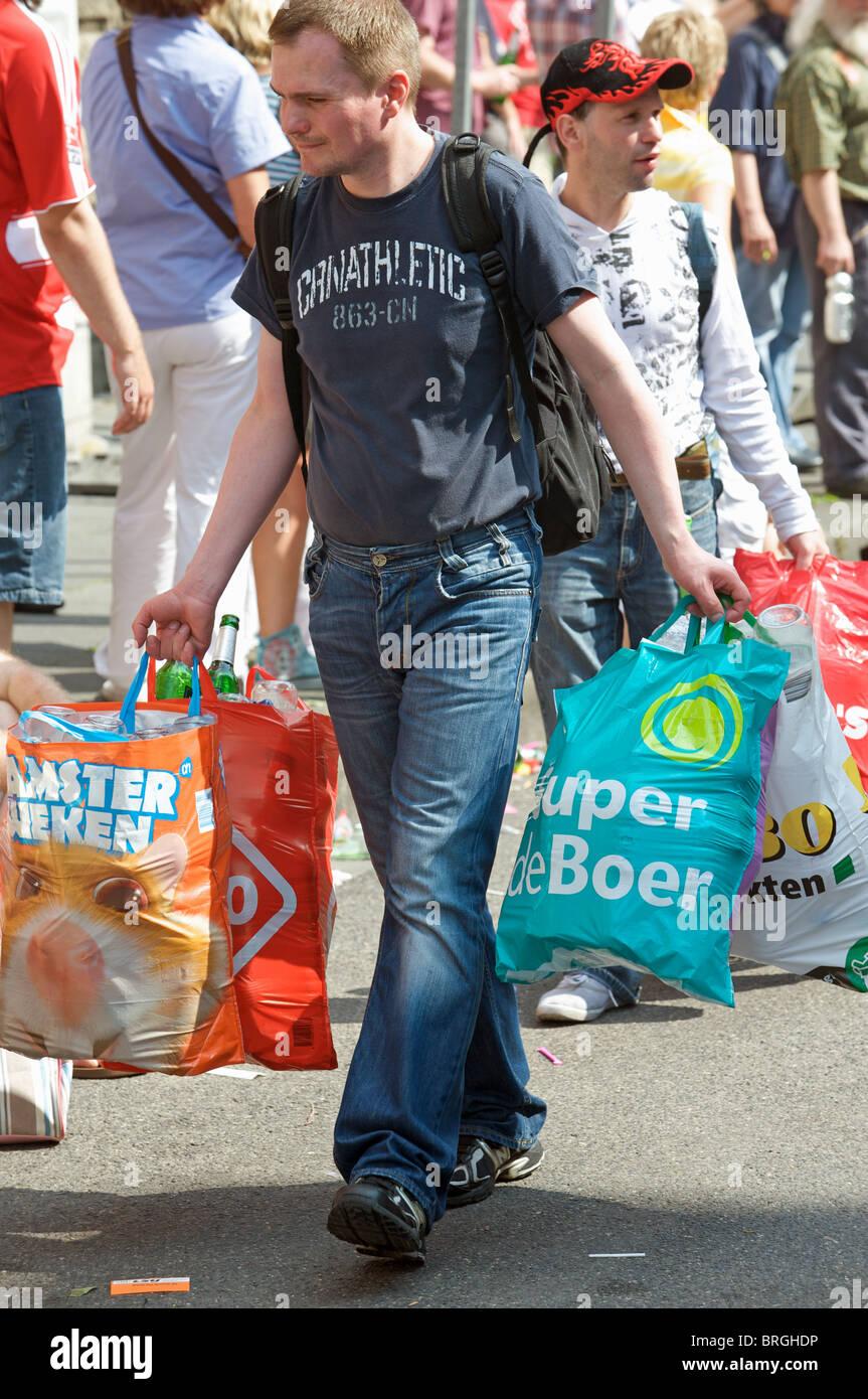 Gli uomini disoccupati la raccolta di bottiglie di vetro dopo una fiera di Colonia, Germania. Immagini Stock
