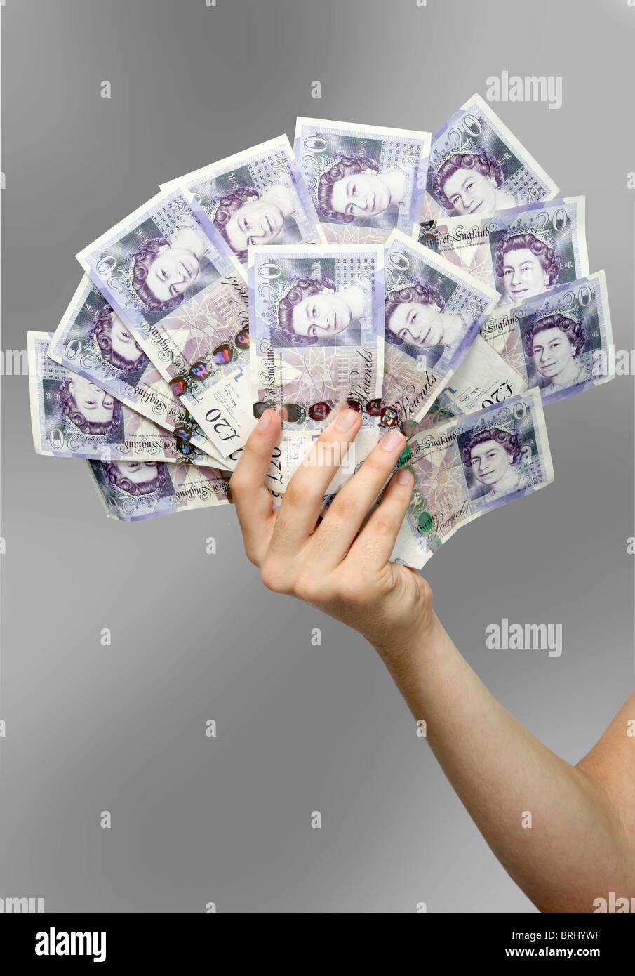 British £20 note essendo tenuto dalla mano maschio Immagini Stock