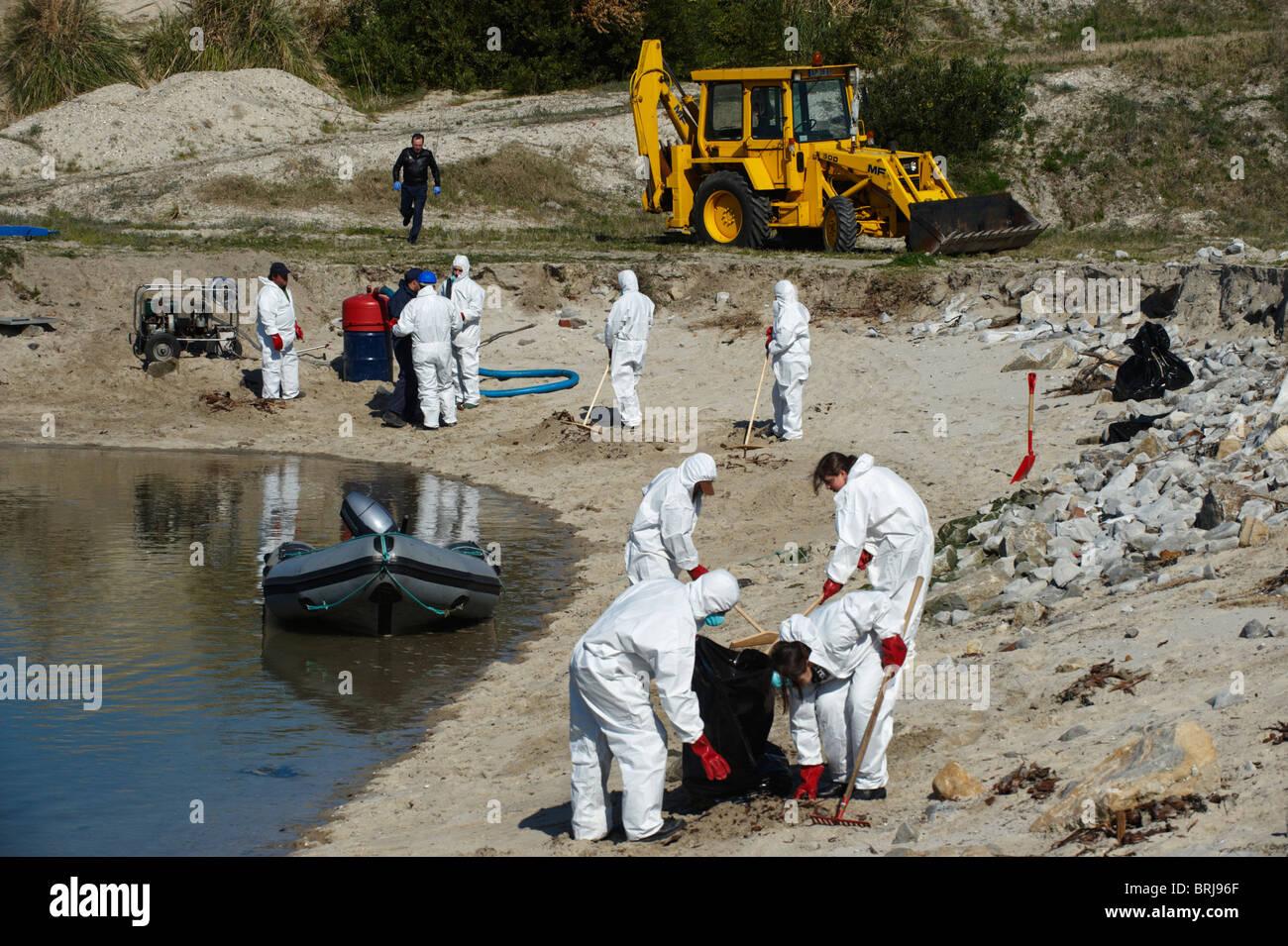Gli uomini in pieno-corpo Indumenti di protezione e le maschere di respirazione pulire una spiaggia Immagini Stock