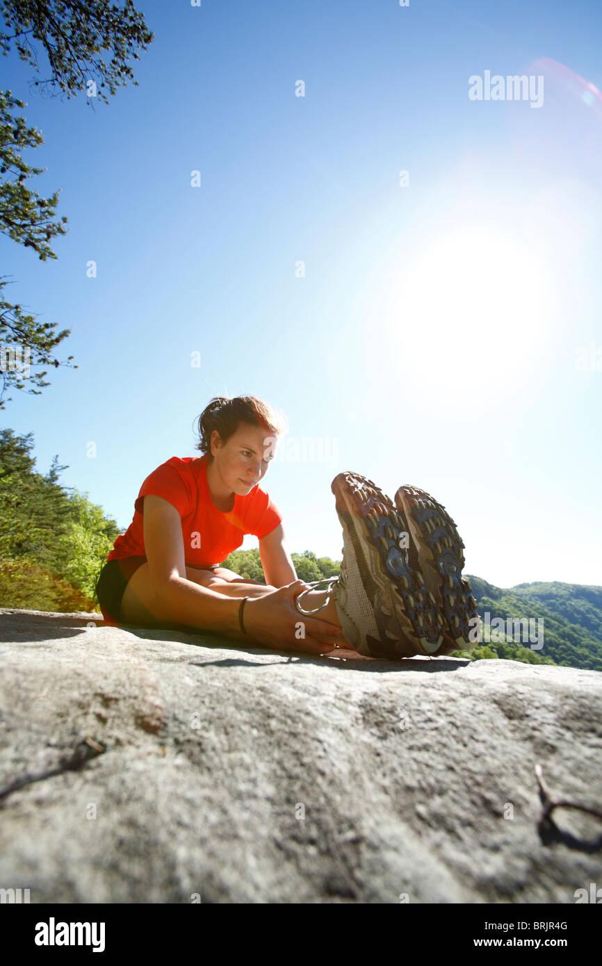 La donna si allunga su una cima prima di trail running in una lussureggiante foresta verde. Immagini Stock