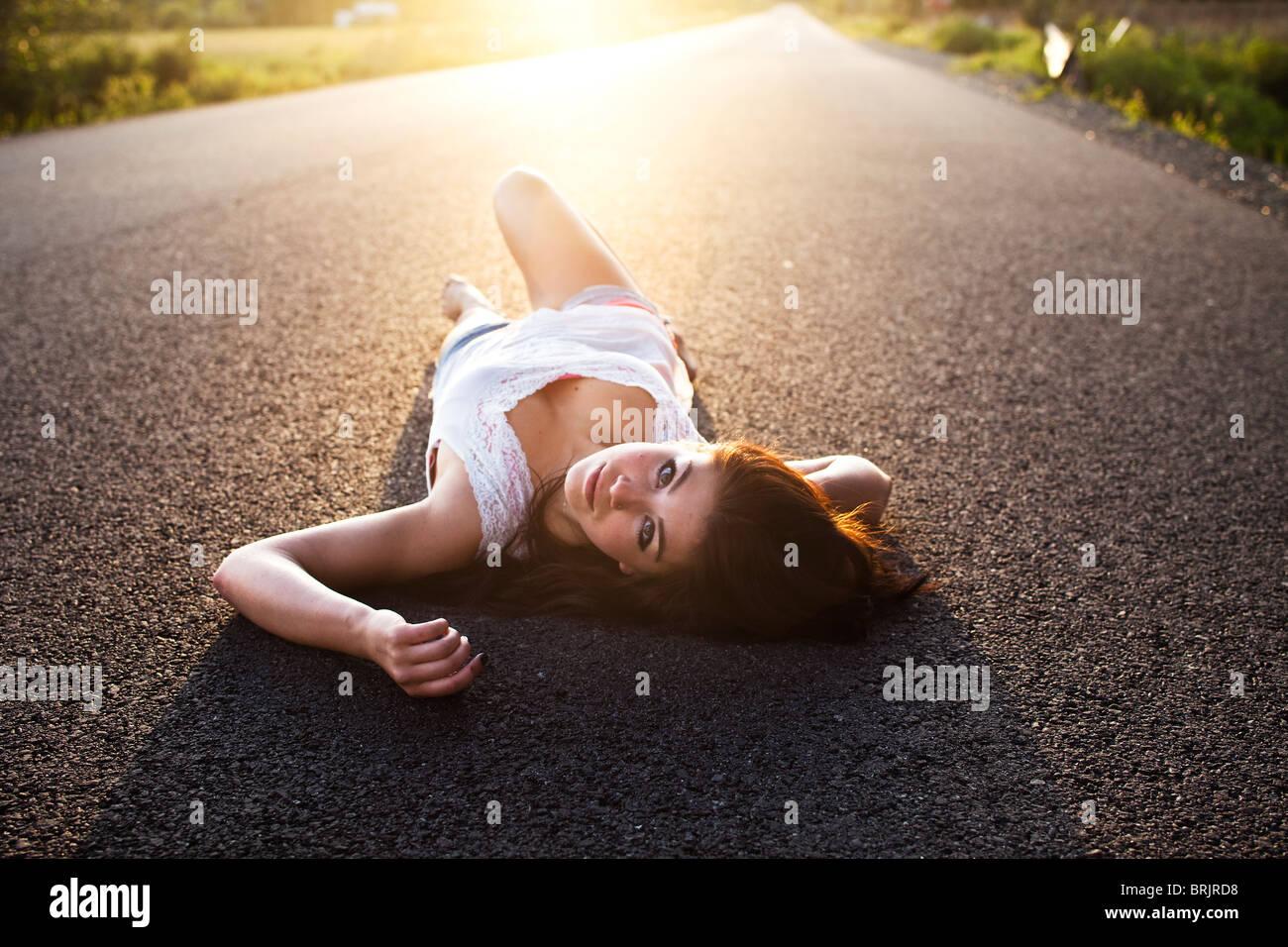 Una ragazza si trova sulla strada al tramonto in Idaho. Immagini Stock