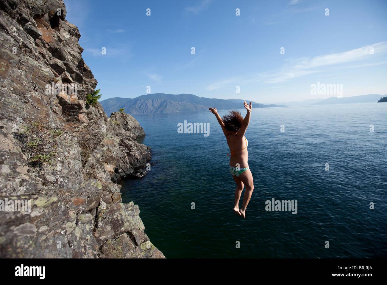 Donna salta fuori da piccola scogliera in un lago in Idaho. Immagini Stock