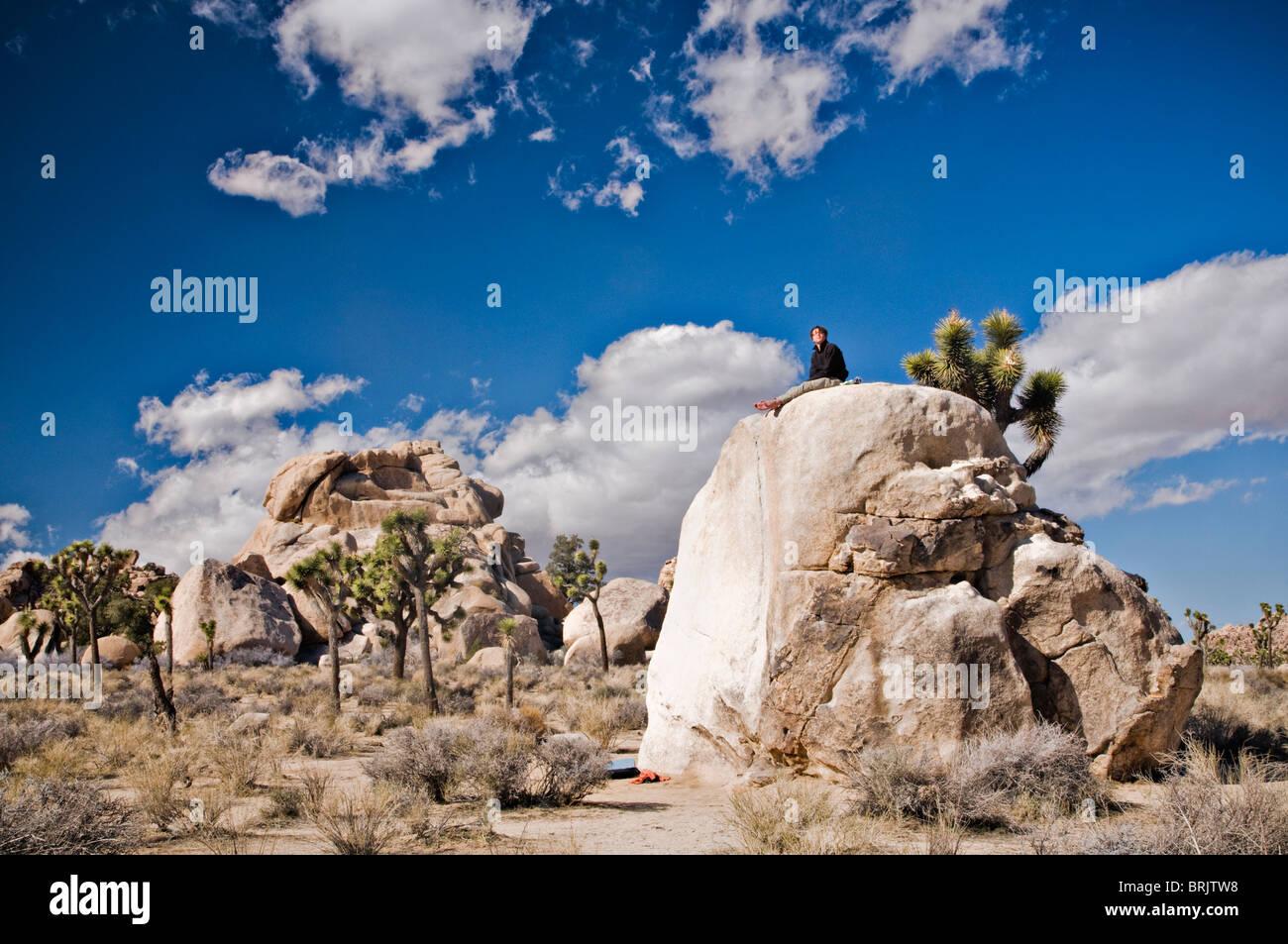 Un giovane uomo si siede su una solitaria bolder dopo la scalata di un percorso nel Parco nazionale di Joshua Tree. Immagini Stock