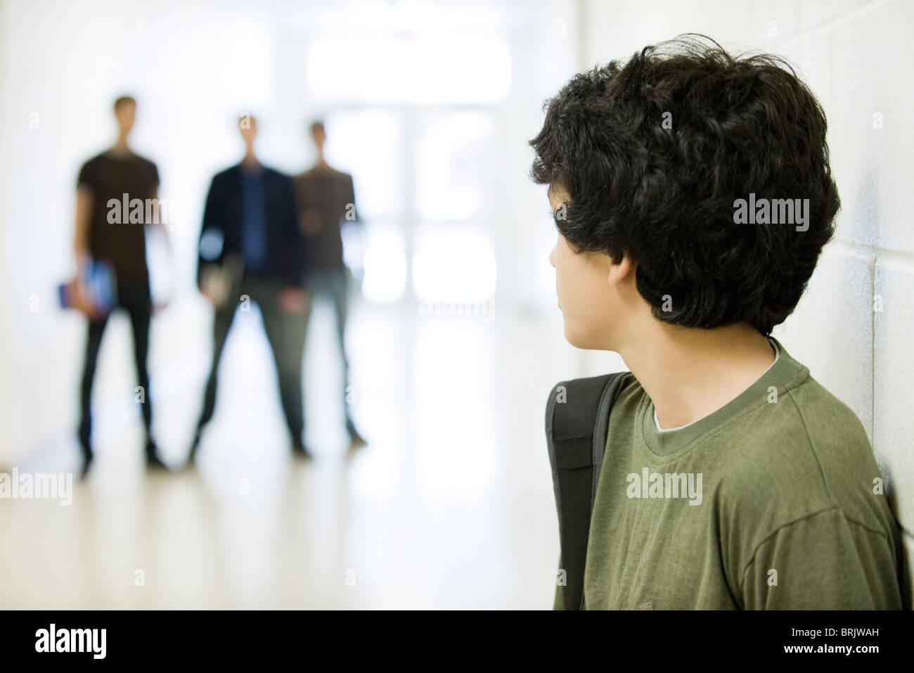 Ragazzo adolescente guardando sopra la spalla al Bulli in background Immagini Stock