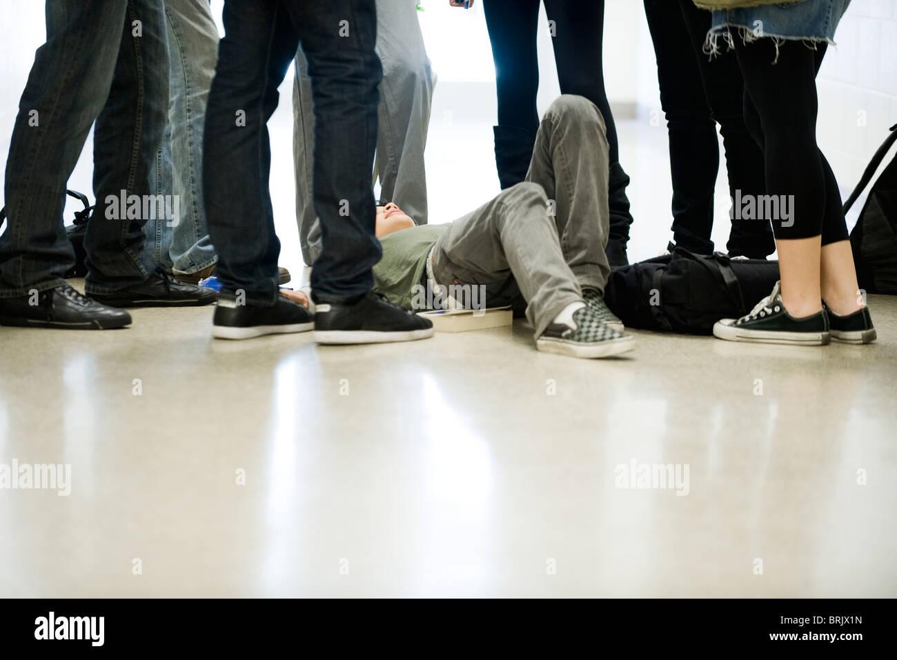 I bulli che circonda e minaccioso ragazzo adolescente sdraiato sul pavimento Immagini Stock