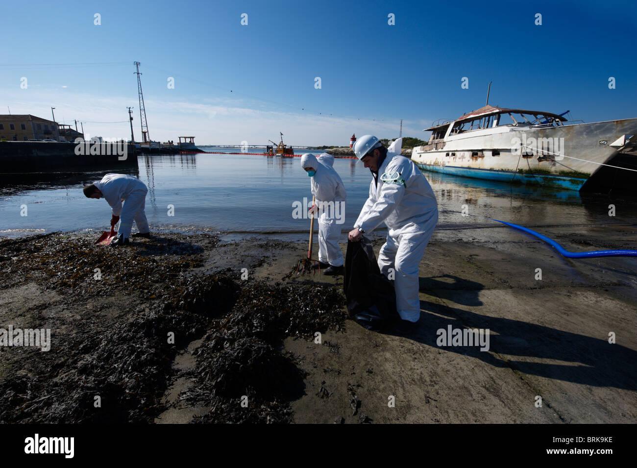 Gli uomini in pieno-corpo Indumenti di protezione e le maschere di respirazione pulire il dock mentre una barca Foto Stock