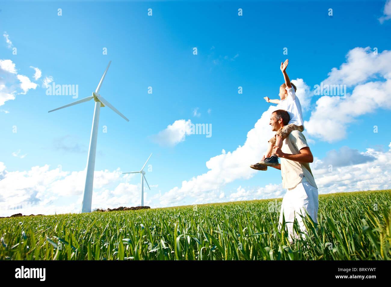 Più lontano e figlio guardando alla turbina eolica Immagini Stock