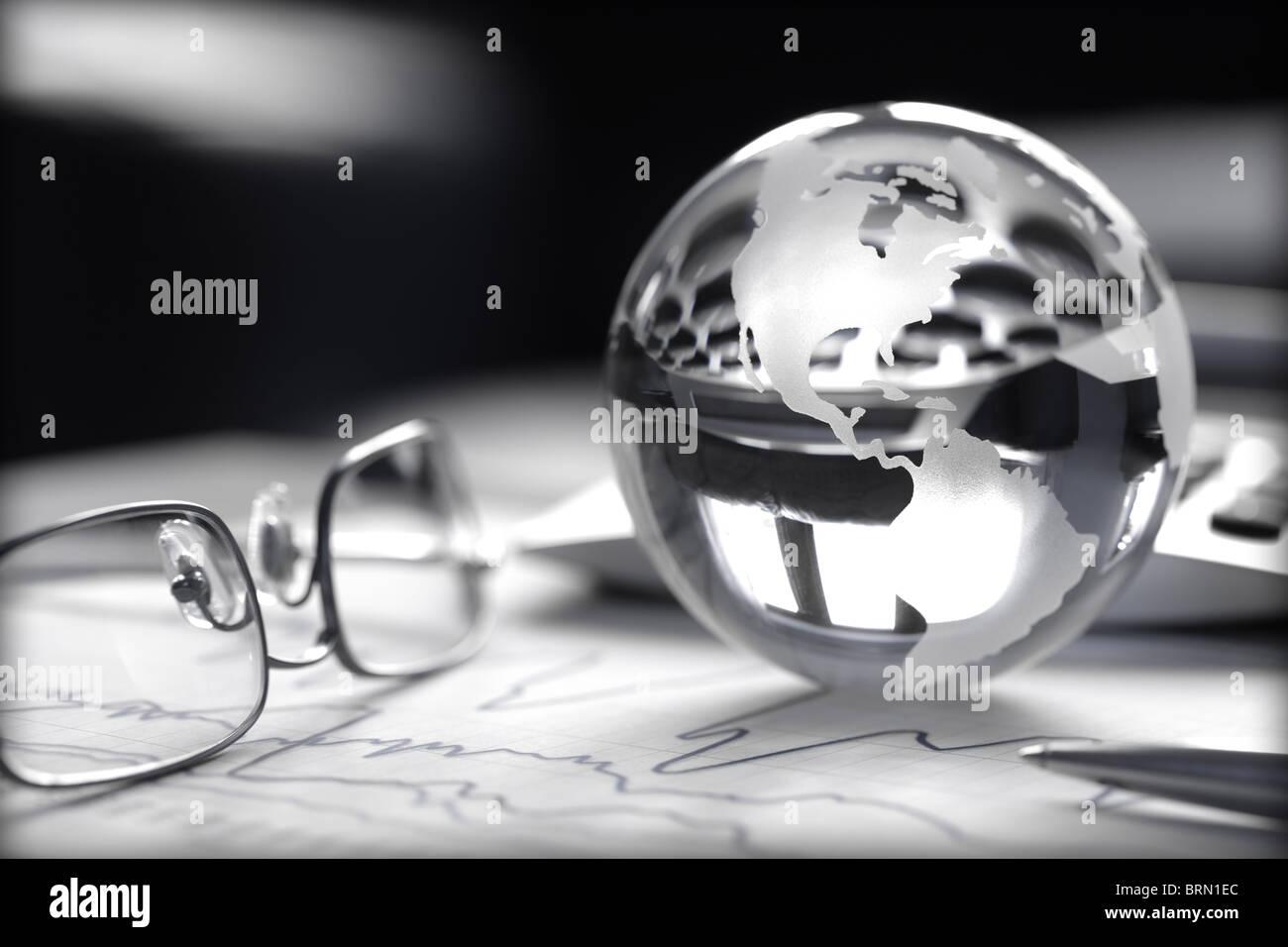 Tonica immagine del globo di vetro con grafici azionari, calcolatrice e spettacoli Immagini Stock
