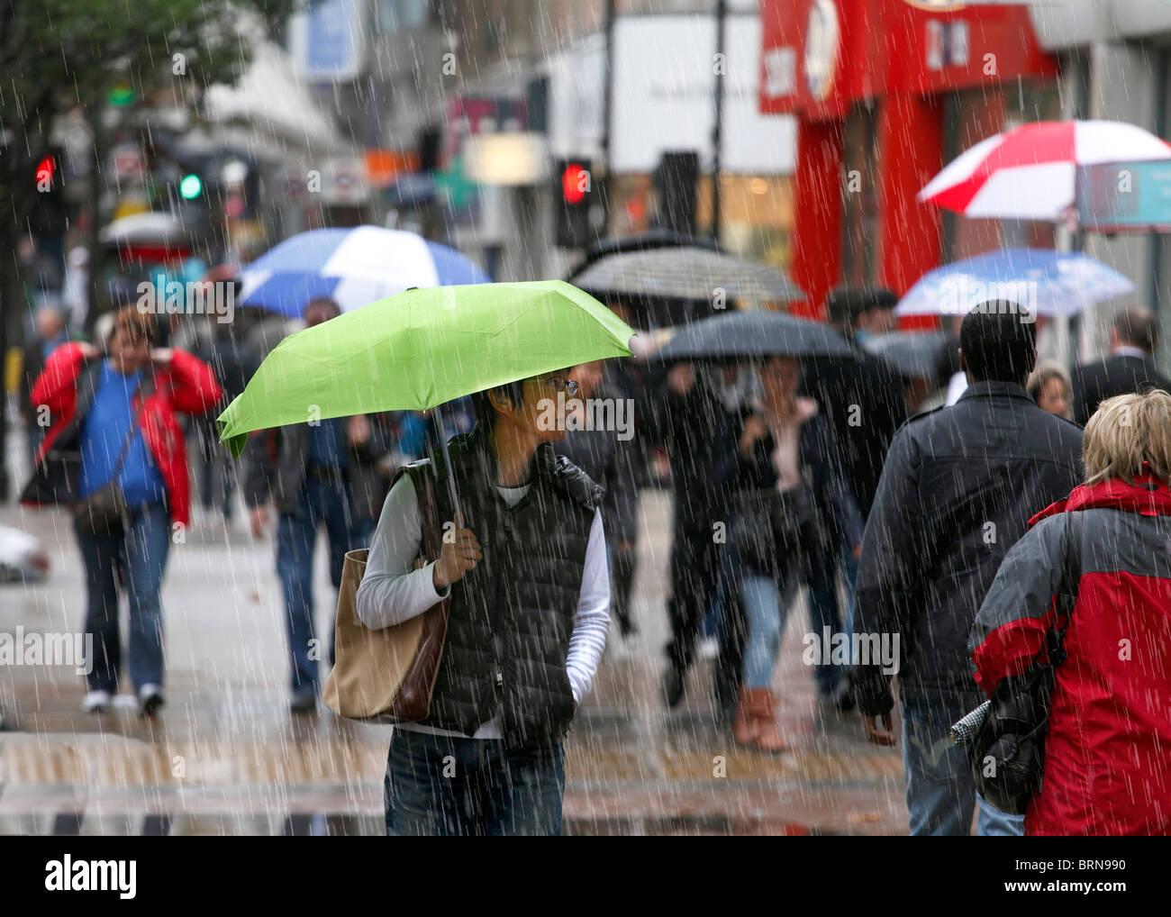 Gli amanti dello shopping in una fredda e piovosa giornata. Immagini Stock