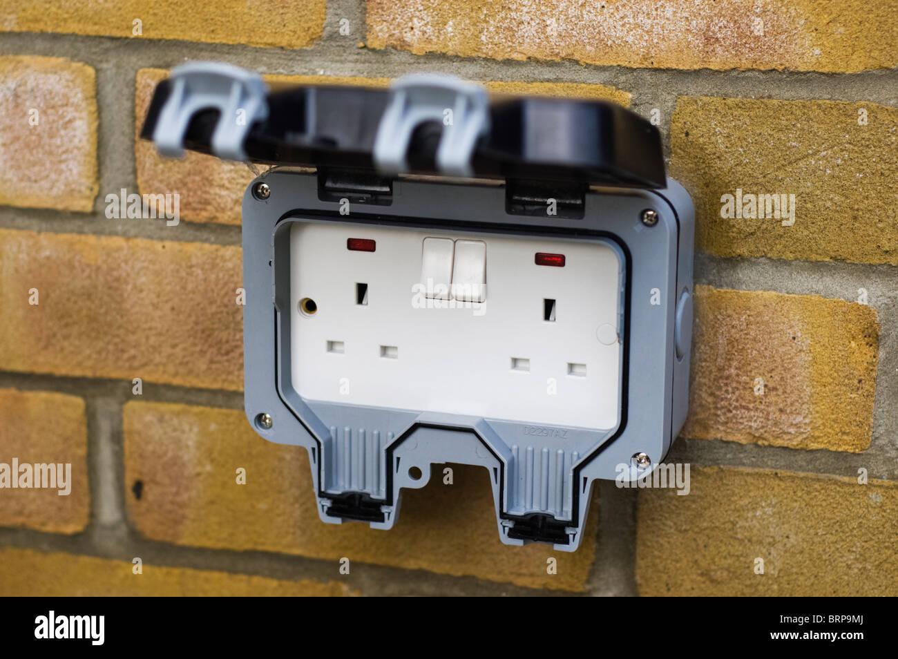 Rete esterna presa di alimentazione per il Regno Unito per la rete elettrica collegata ad una parete di mattoni. Immagini Stock