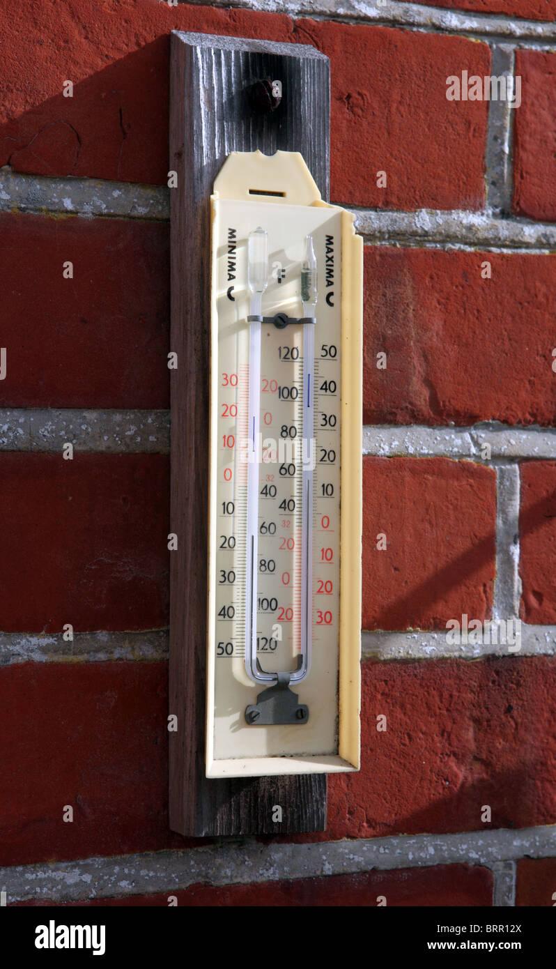 Un minimo di termometro a massima su una parete in un giardino Foto Stock