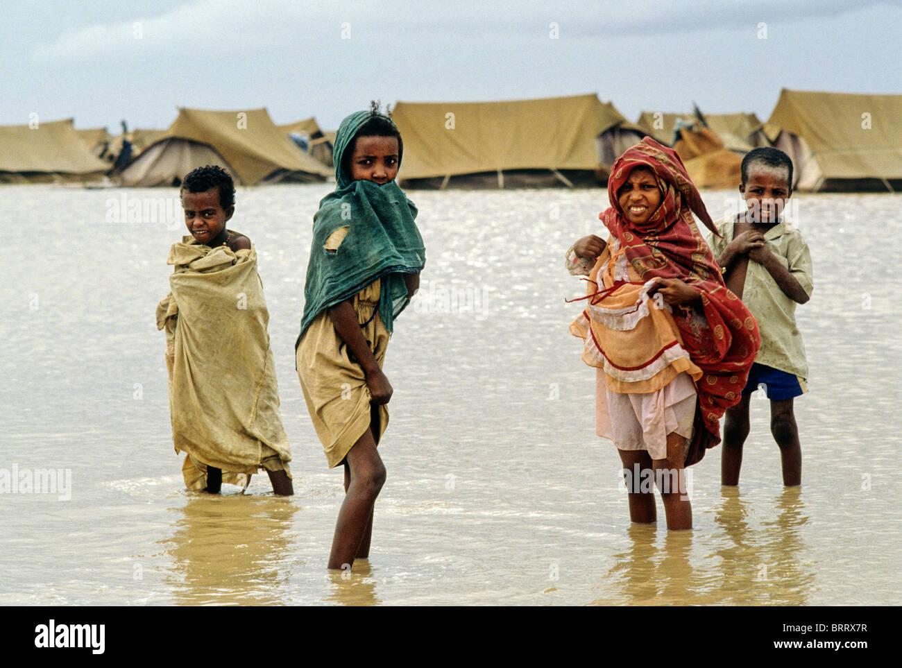 La carestia nella regione del Darfur del Sudan, 1985. I bambini giocano in acqua dopo unseasonable piogge pesanti Immagini Stock
