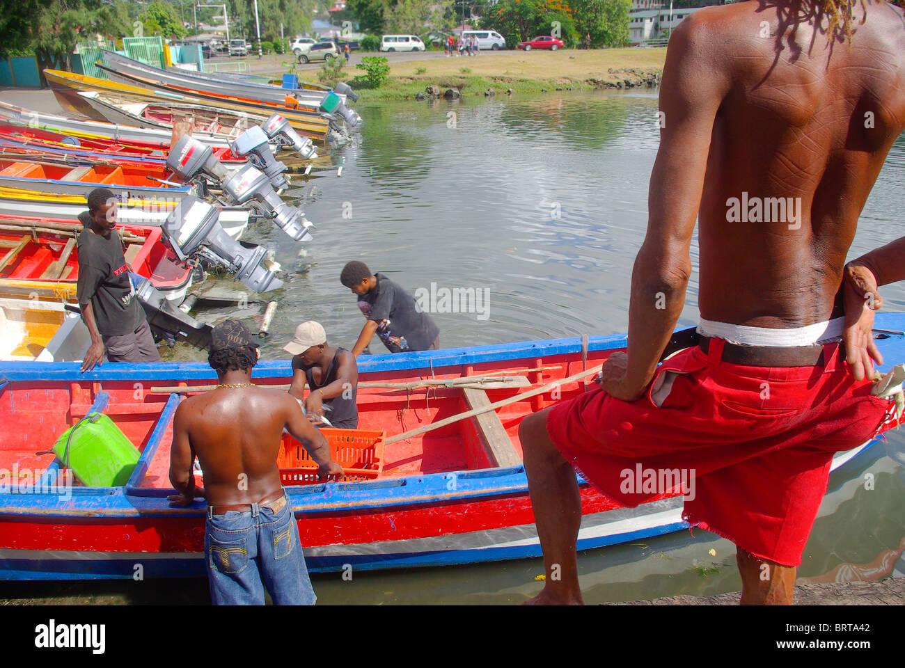 I pescatori tirando barca a riva a Castries complesso di pesca Saint Lucia mentre un curioso sta a guardare Immagini Stock