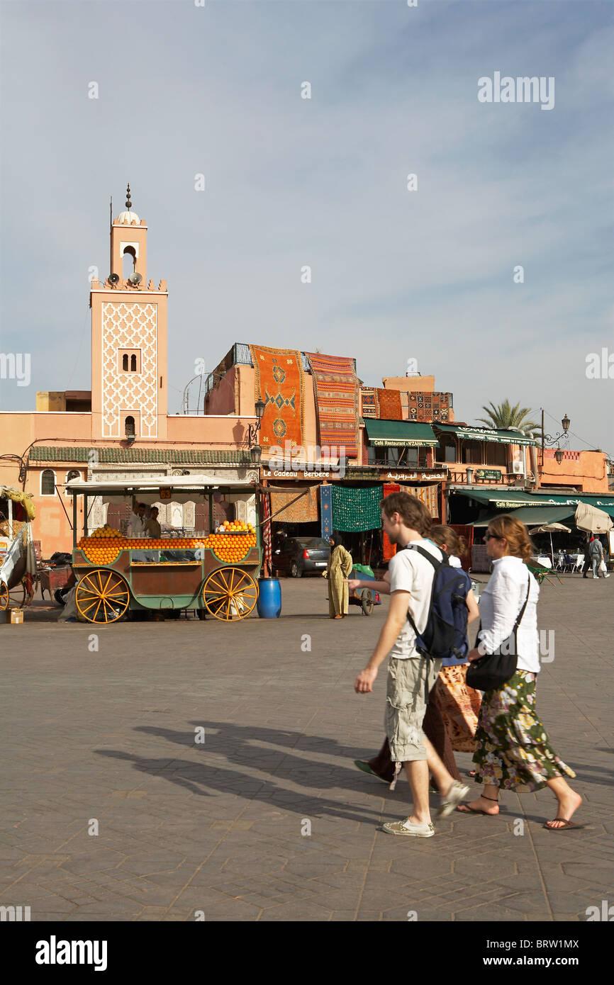 Marrakech: i turisti a piedi attraverso Djemaa el Fna Immagini Stock