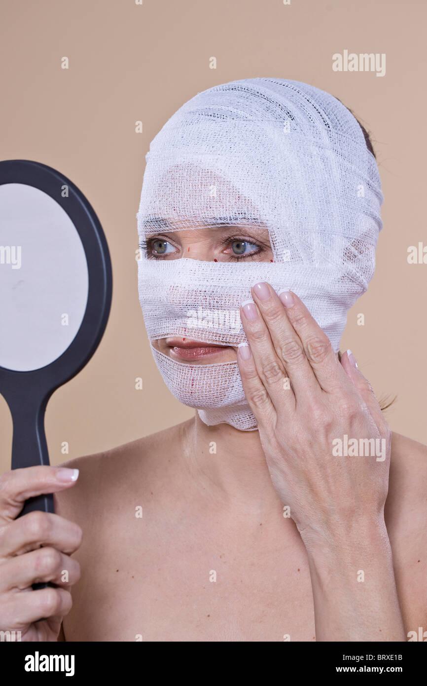 Donna controllando il suo volto benda con un specchio a mano Foto Stock