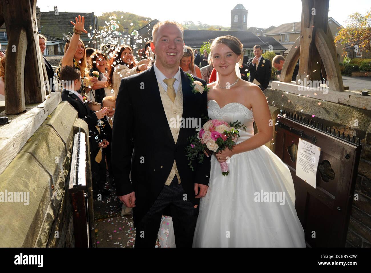 Una giovane sposa e lo sposo sono i residui di carta gettata su di loro il giorno delle nozze Immagini Stock
