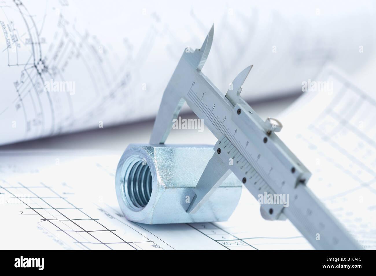 Immagine del righello architettonico sopra il dado con il progetto di casa nelle vicinanze Immagini Stock