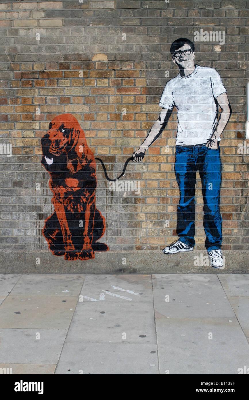 Uomo con cane stencil graffiti banksy stile, shoreditch Londra Immagini Stock