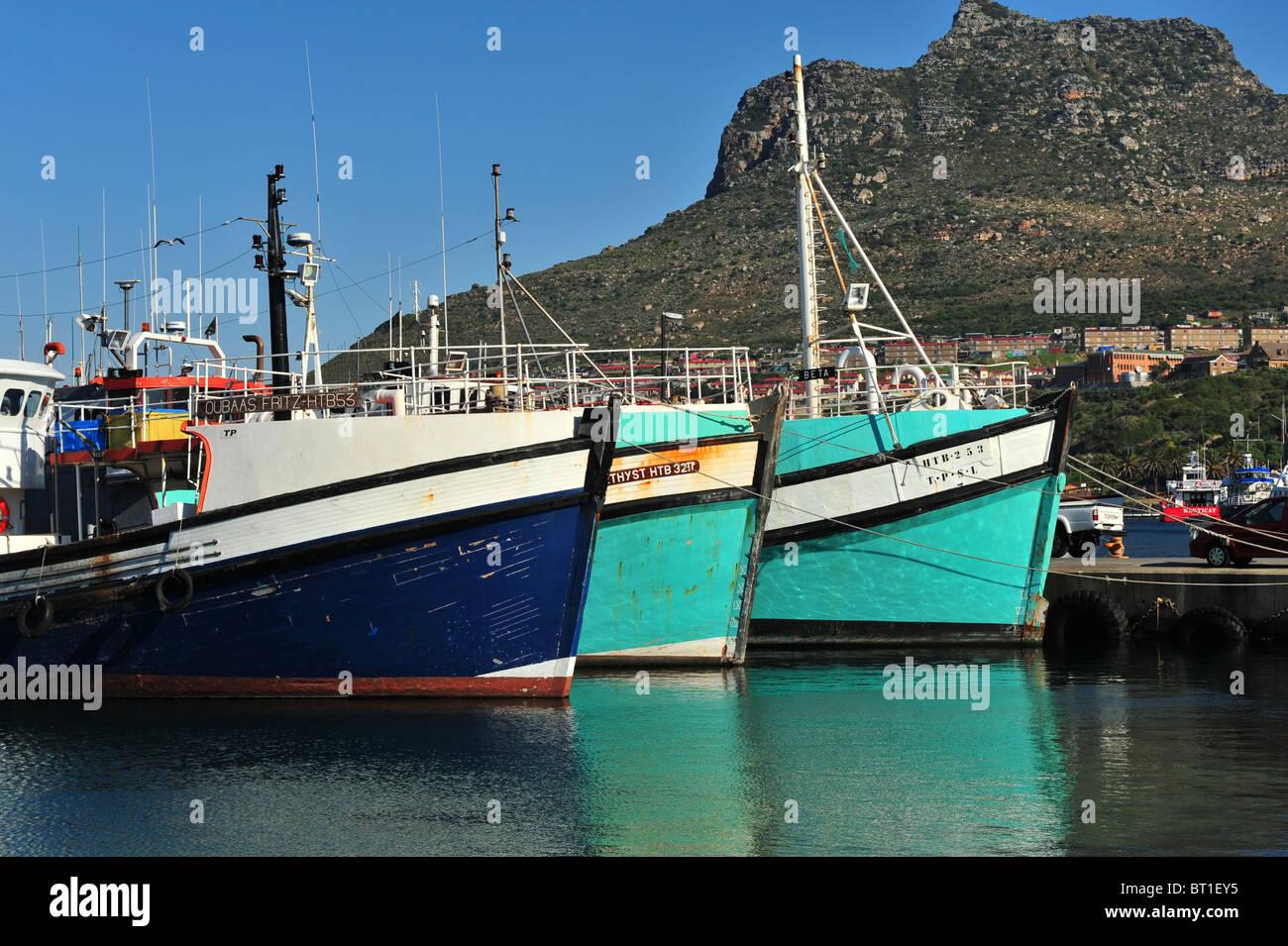 Un ritmo delle colorate barche da pesca riflettente nel blu del mare. Una scena del porto con il cielo blu e una Foto Stock