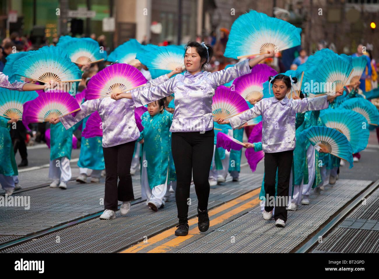 Donna cinese leader di un gruppo di bambini in le prestazioni della ventola durante il Nuovo Anno Cinese parade Immagini Stock