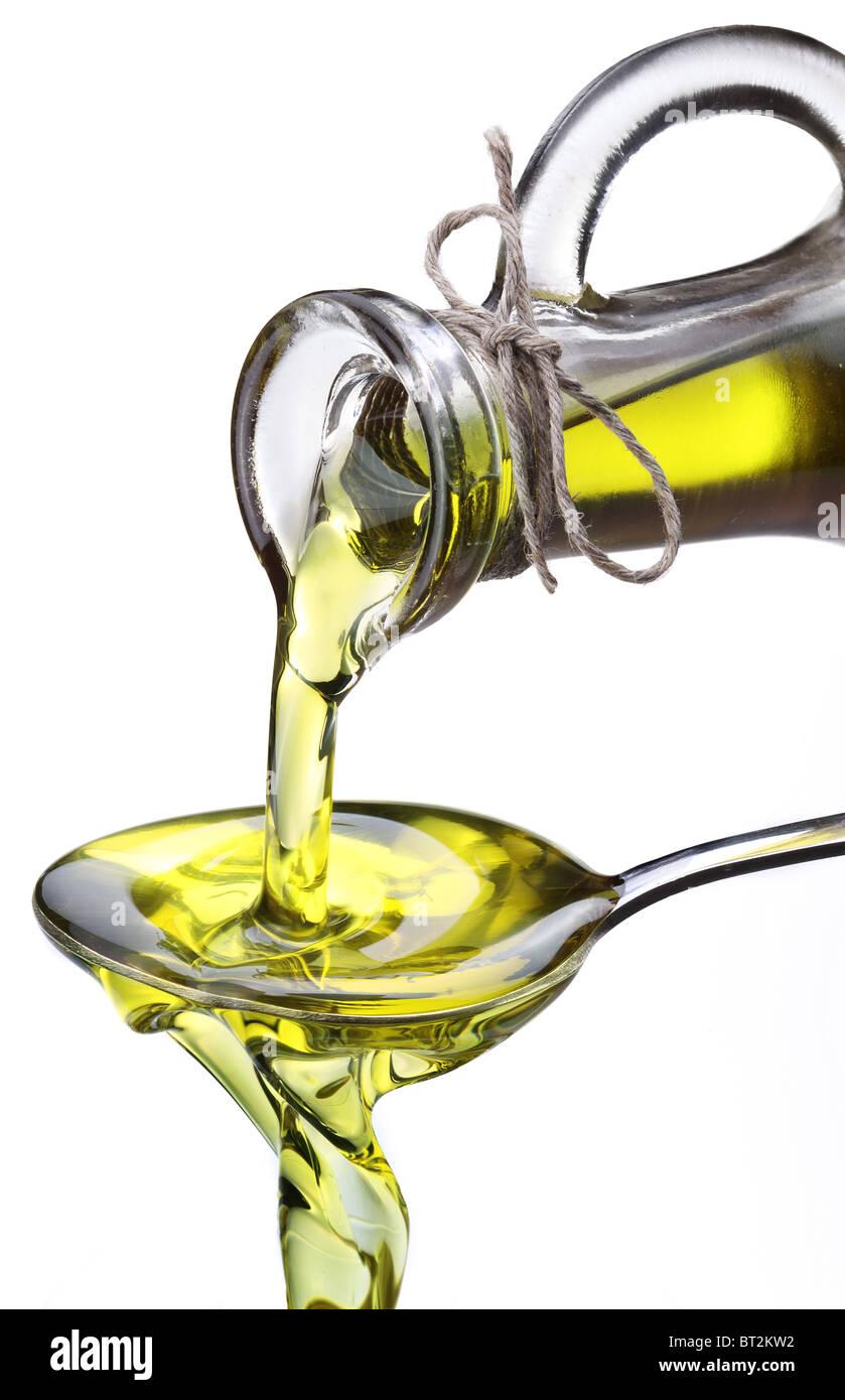 Olio d'oliva che fluisce dalla caraffa in cucchiaio isolate su un bianco. Immagini Stock