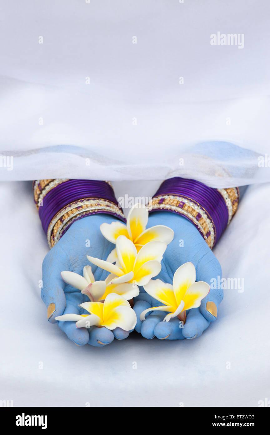 Ragazza indiana con lancette blu e schiave azienda fiori di frangipani Immagini Stock