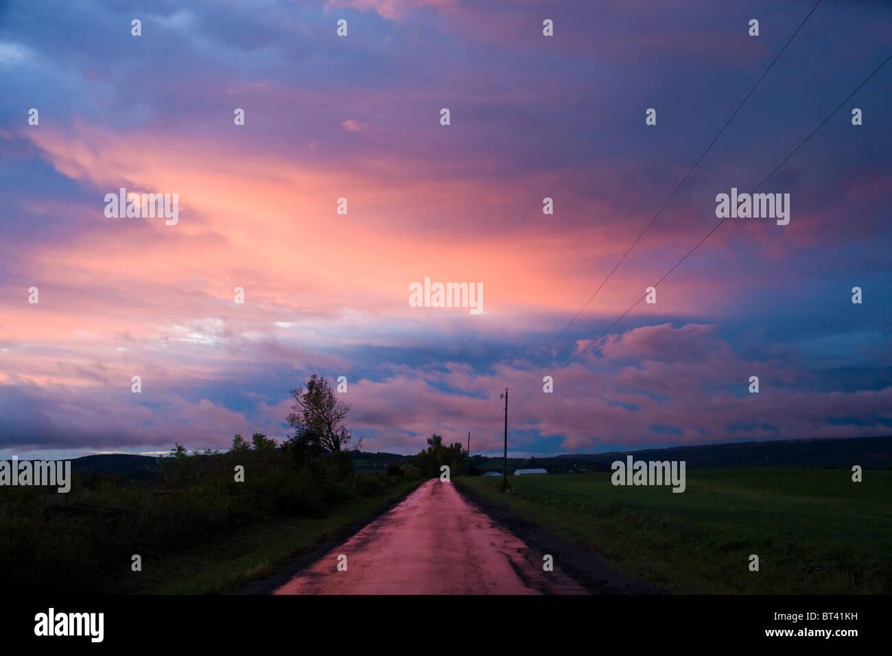 Strada corre nel tramonto, azienda agricola, Mohawk Valley, Herkimer County, nello Stato di New York Immagini Stock