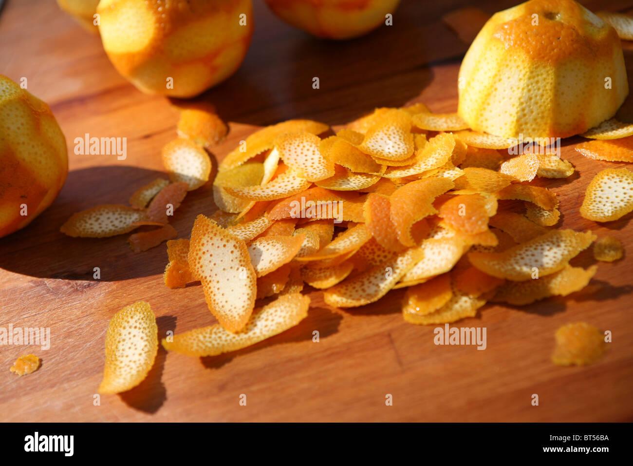 Pila di buccia d'arancia su un tagliere di legno, all'esterno. Immagini Stock