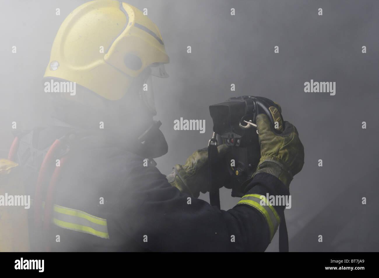 Vigile del fuoco utilizzando una termocamera presso la scena di una proprietà doemsic fire Immagini Stock