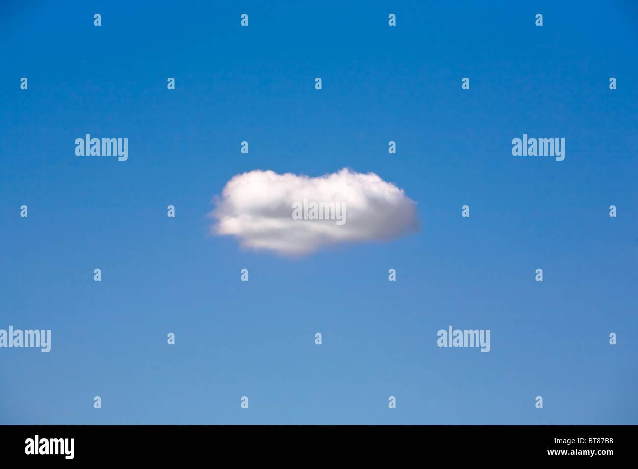 Una singola nuvola galleggianti in un cielo blu. Immagini Stock