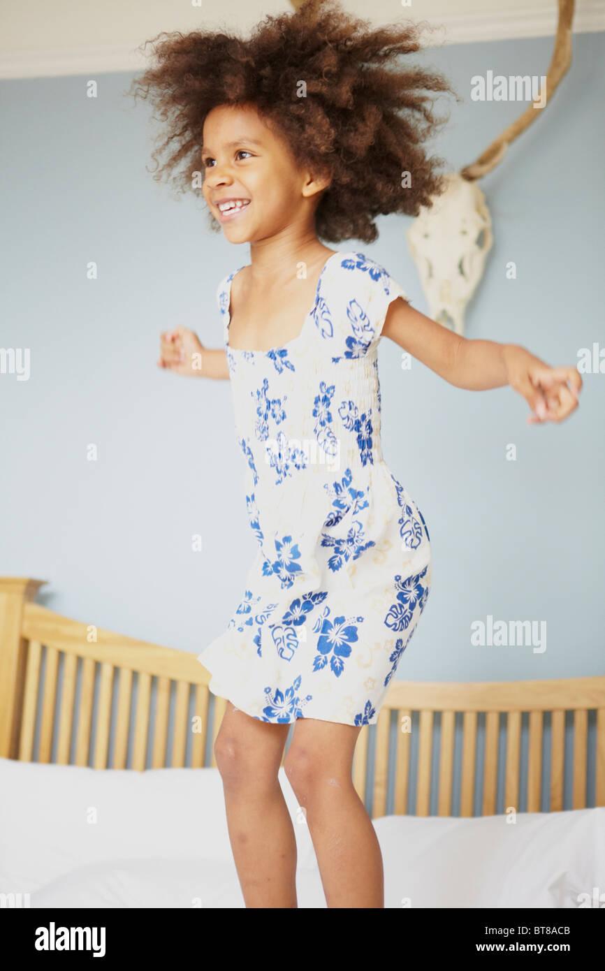 Giovani razza mista ragazza, bambino, saltare sul letto con le braccia aperte e grandi capelli, ridere, sorridente. Immagini Stock