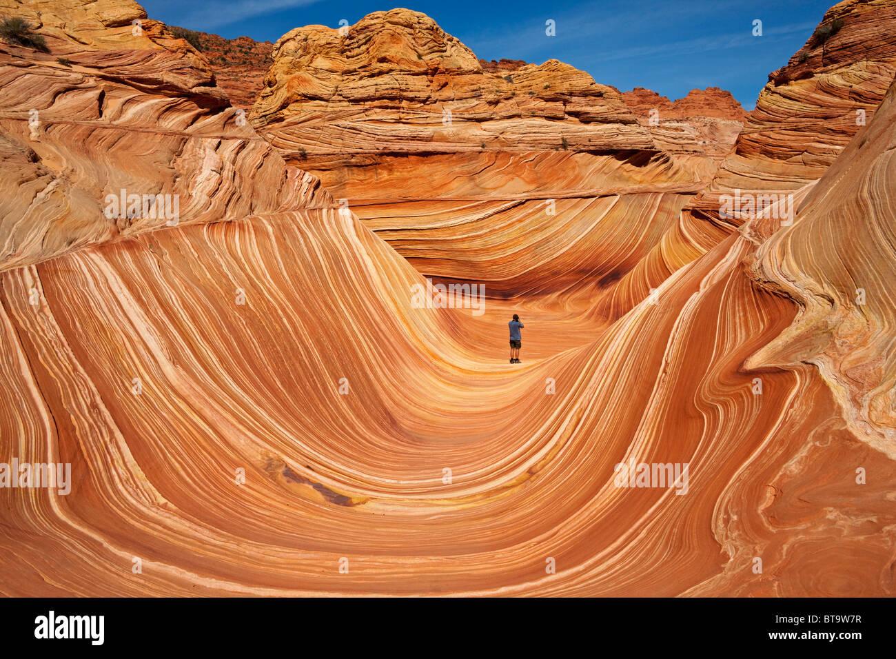 Turisti in onda, formazione di roccia in Coyote Buttes North, Paria Canyon-Vermilion scogliere deserto dello Utah, Immagini Stock